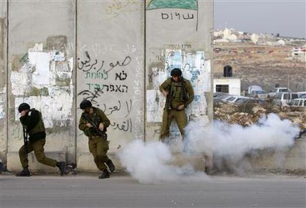 Israeli soldiers take cover after a tear gas canister was mistakenly thrown at them by a comrade during scuffles with Palestinian stone-throwers at Qalandiya checkpoint near the West Bank city of Ramallah December 27, 2008. REUTERS/Ammar Awad
