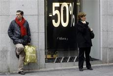 <p>Passanti davanti a un negozio che effettua i saldi. REUTERS/Susana Vera (SPAIN)</p>