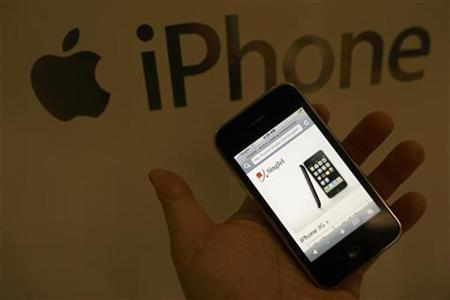 A sales assistant displays an Apple iPhone 3G during its launch at a SingTel store in Singapore early August 22, 2008.REUTERS/Tim Chong