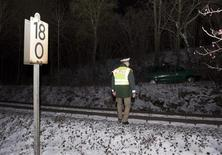 <p>A German police officer walks near the railway track at the site where German billionaire Adolf Merckle committed suicide the previous day near his hometown Blaubeuren, near the southern German city of Ulm January 6, 2009. REUTERS/Wolfgang Rattay</p>