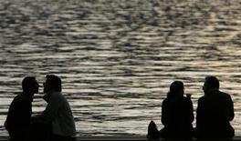<p>People enjoy a warm autumn evening on the edge of the lake of Zurich October 5, 2007. REUTERS/Christian Hartmann</p>