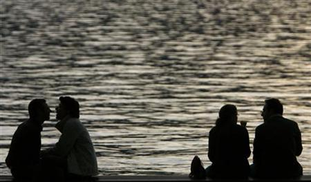 People enjoy a warm autumn evening on the edge of the lake of Zurich October 5, 2007. REUTERS/Christian Hartmann