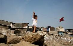 <p>A child flies a kite at the Nehru Nagar slum in Mumbai January 13, 2009. REUTERS/Punit Paranjpe</p>