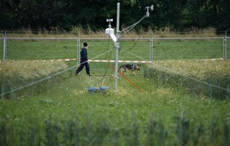 A security guard patrols next to a genetically modified organism (GMO) experimental area outside Zurich July 7, 2008. REUTERS/Christian Hartmann