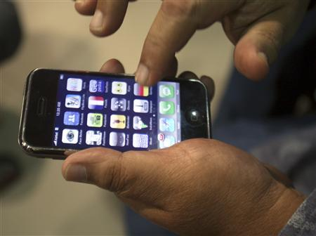 A customer examines his new Apple iPhone 3G at Telcel Center in the eastern Indian city of Kolkata August 21, 2008. REUTERS/Jayanta Shaw