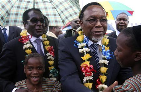 South African President Kgalema Motlanthe (R) greets school children with Zimbabwean President Robert Mugabe (L) at Harare International Airport January 19, 2009. REUTERS/Stringer