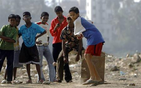 Children play cricket at the Nehru Nagar slum in Mumbai January 13, 2009. REUTERS/Punit Paranjpe