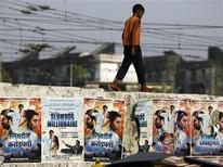 "<p>A boy living on the street walks on a wall displaying publicity posters of Golden Globe award-winning film ""Slumdog Millionaire"" as a train goes past in Mumbai January 22, 2009. REUTERS/Arko Datta</p>"