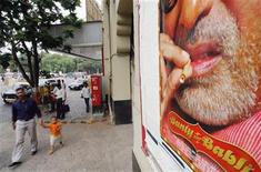 <p>A man and a child walk past an advertisement showing Bollywood star Amitabh Bachchan smoking, in Bombay, India June 1, 2005. REUTERS/Arko Datta</p>