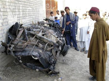 Tribesmen look at a vehicle destroyed by a missile attack in Mir Ali on the outskirts of Miranshah, near the Afghan border, November 1, 2008. REUTERS/Haji Mujtaba