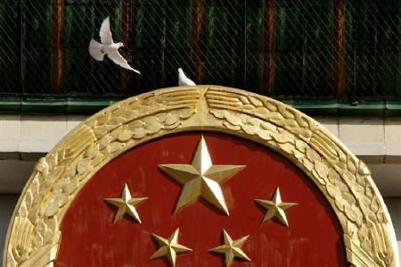 A pigeon flies above the national emblem on the Great Hall of the People in Beijing in this October 21, 2007 file photo. REUTERS/Claro Cortes IV