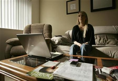 Christine Chase, 24, sits at her computer in her apartment in Campbell, California December 8, 2008. Chase was laid off from her contractor job at AT&T in the Silicon Valley in August. REUTERS/Robert Galbraith