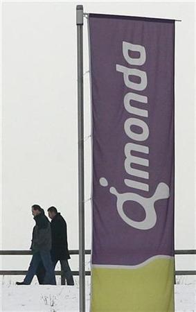 People walk behind flags of German memory chip maker Qimonda in Munich, January 23, 2009. REUTERS/Alexandra Beier