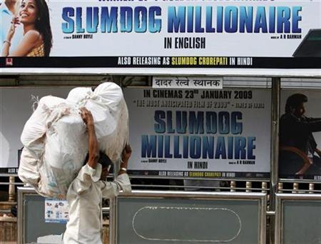 A worker walks past a billboard of Golden Globe award winning flim 'Slumdog Millionaire' displayed at a bus station in Mumbai January 29, 2009. REUTERS/Arko Datta