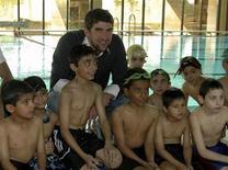 <p>El nadador olímpico Michael Phelps posa con niños en una piscina en Riyadh, Arabia Saudita, 27 ene 2009. El Comité Olímpico Internacional (COI) dijo que unas disculpas del múltiple campeón olímpico de natación Michael Phelps, quien fue fotografiado inhalando de una pipa que se utiliza para fumar marihuana, eran una prueba suficiente de su sinceridad. REUTERS/Stringer</p>