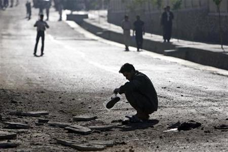 A crime investigating team works at the site after a suicide bombing in Kabul July 22, 2008. A suicide bomber killed three civilians and wounded one more in an attack in the Afghan capital, Kabul, a police official said. REUTERS/Ahmad Masood