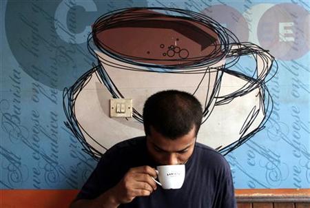 A man drinks coffee at a coffee shop in Mumbai May 9, 2006. REUTERS/Adeel Halim