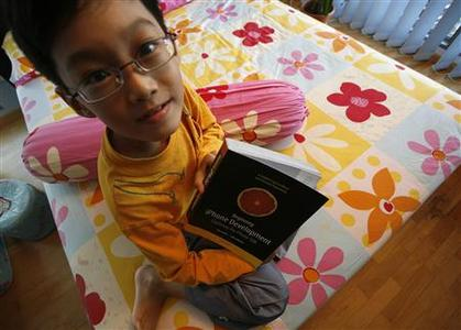 Nine-year-old Lim Ding Wen holds a book on iPhone programming at his home in Singapore, February 6, 2009. REUTERS/Vivek Prakash