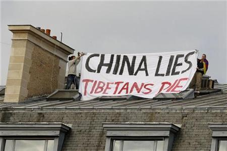 Pro-Tibetan activists hold a banner on the roof of a building near the Chinese embassy in Paris, August 23, 2008. REUTERS/Benoit Tessier