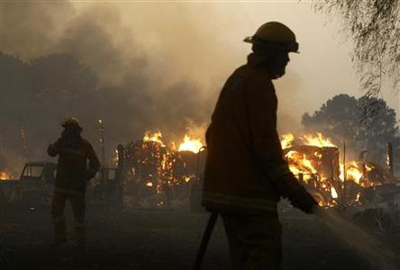 Firemen extinguish a bushfire while a shed burns on the outskirts of Labertouche, 90km (56 miles) east of Melbourne February 7, 2009. REUTERS/Mick Tsikas