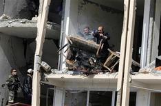<p>Сотрудники полиции Афганистана выкидывают сгоревшую мебель из здания, атакованного боевиком-смертником, в Кабуле 11 февраля 2009 года. Боевик-смертник экстремистского движения Талибан совершил взрыв в правительственном здании в центре Афганской столицы в среду. Вблизи президентского дворца слышны выстрелы, сообщают свидетели и полиция. REUTERS/Omar Sobhani</p>