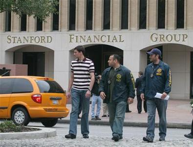 United States Marshals cross the street to Stanford Financial Group's office tower in the upscale Galleria District of Houston, with the firm's second Galleria District building in the background, February 17, 2009. REUTERS/Donna Carson