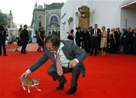 Mickey Rourke arrives with his dog Loki for the award ceremony of the Venice Film Festival September 6, 2008. REUTERS/Denis Balibouse