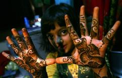 "<p>Rubina Ali, who acted as young Latika in the film ""Slumdog Millionaire"" shows mehndi painted on her hands in the slum she resides in, prior to leaving for airport to fly to Los Angeles to attend the 81st Academy Awards, in Mumbai February 20, 2009. REUTERS/Arko Datta</p>"