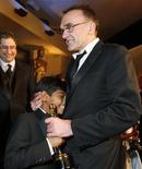 """<p>Il regista Danny Boyle (a destra) abbraccia l'attore di """"The Millionaire"""" Azharuddin Mohammed Ismail. REUTERS/Lucas Jackson</p>"""