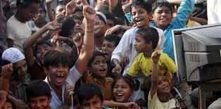 """<p>Vecinos de Azharuddin Ismail que participaron en la filmación de """"Slumdog Millionaire"""", celebran mientras observan la octegésima primer entrega de los premios de la Academia en Mumbai, 23 feb 2009. Bollywood conoció verdaderamente a Hollywood el lunes cuando los residentes de los barrios pobres de Mumbai celebraron el triunfo de """"Slumdog Millionaire"""" en los premios Oscar, aplaudiendo, gritando y bailando como las estrellas del cine indio. REUTERS/Arko Datta (INDIA)</p>"""