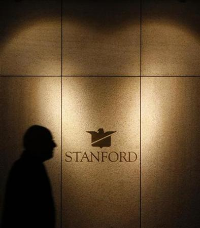 A man is silhouetted as he walks past the Stanford Group AG building in Zurich, February 18, 2009. REUTERS/Christian Hartmann