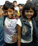 """<p>Azharuddin Ismail (sinistra) e Rubina Ali, i due bambini indiani che nel film vincitore di otto Oscar """"The Millionaire"""" interpretano Salim e Latika, incontrano gli amici al ritorno nella loro baraccopoli a Mumbai. REUTERS/Punit Paranjpe</p>"""