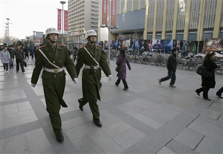 Security officers patrol on a street in Wangfujing after three men set themselves on fire, in Beijing February 25, 2009. REUTERS/Alfred Cheng Jin