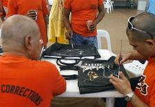 <p>Detenuti decorano alcune borse durante un laboratorio dello stilista Puey Quinones al carcere New Bilibid nelle Filippine. REUTERS/Romeo Ranoco (PHILIPPINES)</p>