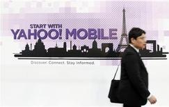 <p>Immagine d'archivio di un passante davanti a una pubblicità di Yahoo. REUTERS/Albert Gea (SPAIN)</p>