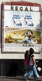 People walk past film posters of ''Slumdog Millionaire'' and ''Delhi 6'', a Bollywood film, at a movie theatre in Mumbai March 1, 2009. REUTERS/Arko Datta