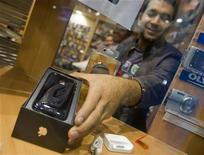 <p>Un negoziante mostra un iPhone della Apple. REUTERS/Morteza Nikoubazl</p>