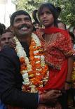 """<p>Foto de archivo de Rajendra Sonekar junto a su hija, Pinki, a su llegada a un hospital de Varanasi, India, donde fue sometida a una cirugía, 28 feb 2009. No es tan famosa como los actores de """"Slumdog Millionaire"""", pero Pinki Sonkar es una leyenda en la aldea que una vez la marginó, gracias a la cirugía que corrigió su fisura de paladar y a su participación en el filme que ganó el segundo Oscar de este año para India. REUTERS/Pawan Kumar (INDIA)</p>"""
