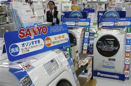An employee walks near Panasonic Corp (R) and Sanyo Electric Co Ltd washing machines at a Sofmap electronics store in Tokyo November 4, 2008. Shares in Panasonic Corp jumped nearly 5 percent on Tuesday, after sources said it planned to buy smaller rival Sanyo Electric Co Ltd to create Japan's largest electronics maker. REUTERS/Toru Hanai