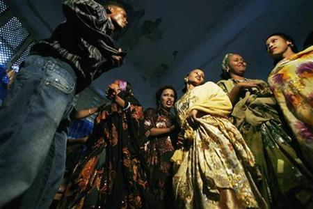 Somali women dressed in brightly coloured gowns with golden jewellery and elaborate hairstyles dance with men to a slow tune of Somali love songs in this July 25, 2007, file photo. REUTERS/Edward Ou