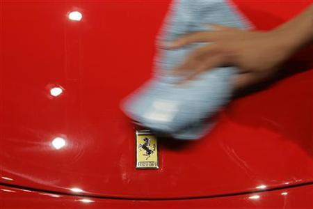 An employee wipes a Ferrari F430 Spider which is on display during the first media day of the 77th Geneva car show at the Palexpo in Geneva March 6, 2007. REUTERS/Stefan Wermuth
