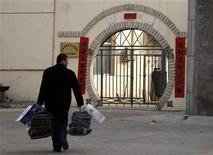 <p>Un uomo porta vestiti e cibo in un centro di detenzione a Pechino. REUTERS/David Gray (CHINA)</p>