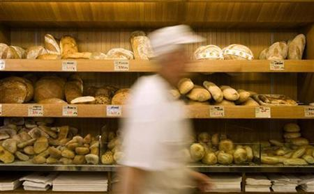 A baker walks past bread inside a bakery in downtown Rome in this file photo from September 18, 2008. REUTERS/Tony Gentile