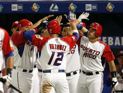 Ramon Vazquez (C) of Team Puerto Rico is congratulated by teammates including catcher Ivan Rodriguez (R) after he scored against Team USA on a hit by teammate Carlos Delgado in the first inning during their second round game at the World Baseball Classic in Miami, Florida March 14, 2009. REUTERS/Hans Deryk