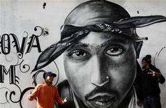"<p>Nuno (L) talks to Sergio Rodrigues ""Sorriso"" next to a graffiti of murdered rapper Tupac Shakur in the Cova da Moura district in Lisbon December 6, 2007. REUTERS/Nacho Doce</p>"