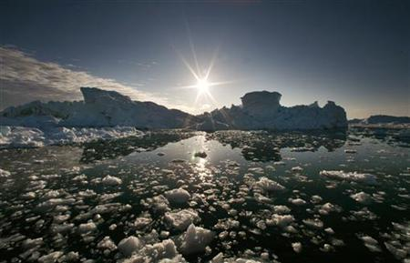 Icebergs are reflected in the calm waters at the mouth of the Jakobshavn ice fjord near Ilulissat in this photo taken May 15, 2007. REUTERS/Bob Strong