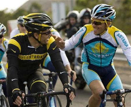 Seven-time Tour de France champion Lance Armstrong of the U.S. (L) talks to 2007 Tour de France winner and team mate Alberto Contador of Spain as they ride together during a training session with Armstrong's new team Astana, in Tenerife, Spain's Canary Islands, December 5, 2008. REUTERS/Paul Hanna