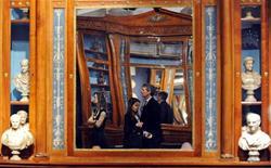 <p>Pessoas refletidas em um par de estante de livros de madeira italiana rara em uma exibição dos pertences pessoais do estilista Gianni Versace na casa de leilões Sotheby's, em Londres. 18/03/2009. REUTERS/Toby Melville</p>