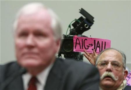 A protester holds up a sign behind AIG CEO Edward Liddy during his testimony before the House Financial Services Subcommittee on Capital Markets, Insurance, and Government Sponsored Enterprises as they hold a hearing on ''American International Group's Impact on the Global Economy: Before, During, and After Federal Intervention'' on Capitol Hill in Washington, March 18, 2009. REUTERS/Jason Reed