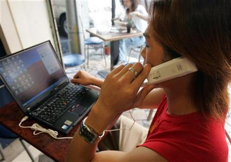 A man uses a Skype internet phone next to a laptop in Taipei, November 11, 2005. REUTERS/Richard Chung